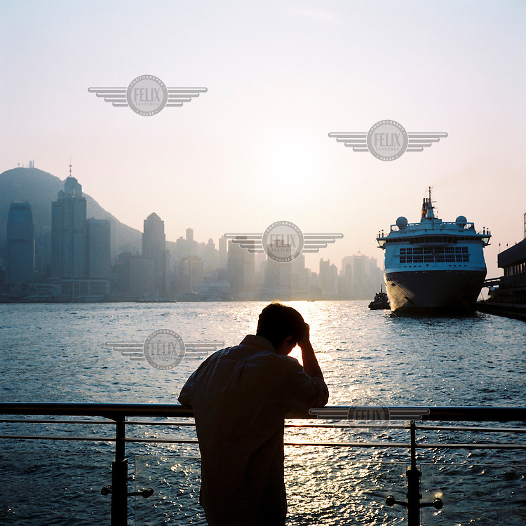 A man looks out over the river and a docked ship in Hong Kong.