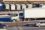 Speeding down a Chicago interstate, a plain white box truck passes a warehouse full of truck trailers.