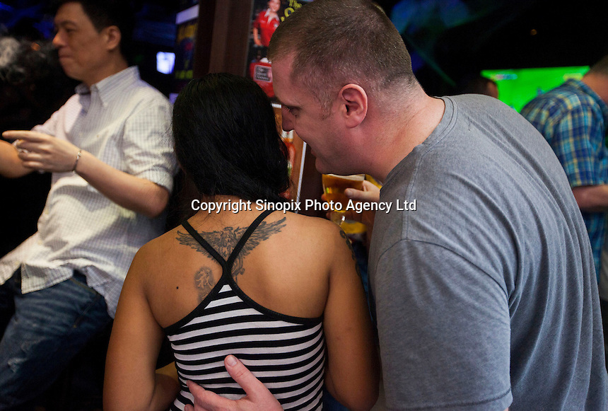 Expats and girls hang around outside bars in Hong Kong's Wanchai area, Sunday 02nd November. A gruesome double murder was discovered yesterday of likely sex workers allegedly by a British banker who lived in the Wanchai District.<br /> <br /> 02-Nov- 2014