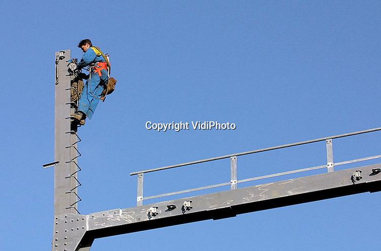 Foto: VidiPhoto..TIEL - In Tiel is dinsdag een begin gemaakt met het spannen van de electriciteitskabels voor de nieuwe masten langs de Betuwelijn. Meer dan tien masten moesten door de aanleg van de lijn, ter hoogte van Tiel, afgebroken worden. Op die plek verdwijnen de kabels in de grond. Ruim een kilometer verder worden ze weer bovengronds geleid via een nieuwe route van hoogspanningsmasten. Het spannen van de kabels duurt enkele weken.