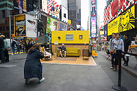 """Tourists pose for photographs in #SetintheStreet, an interactive film set in the middle of Times Square in New York on Friday, April 17, 2015. Created by Justin Bettman, the public art project made out of found items allows visitors to pose for photos in a """"film still"""". The project in Times Square is in collaboration with the Tribeca Film Festival. Between uses found materials and hopes that #SetintheStreet will cause people to re-evaluate their thinking about trash.  (© Richard B. Levine)"""