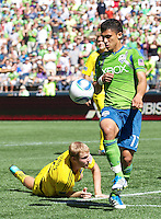 Seattle Sounders FC forward Fredy Montero, right, gets control of the ball in front of a fallen Columbus Crew midfielder Kevin Burns during play at CenturyLink Field in Seattle Saturday Aug. 27, 2011. The Sounders FC won the game 6-2.