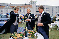 Racegoers in traditional tailcoats having champagne picnic with at Epsom Racecourse on Derby Day, UK