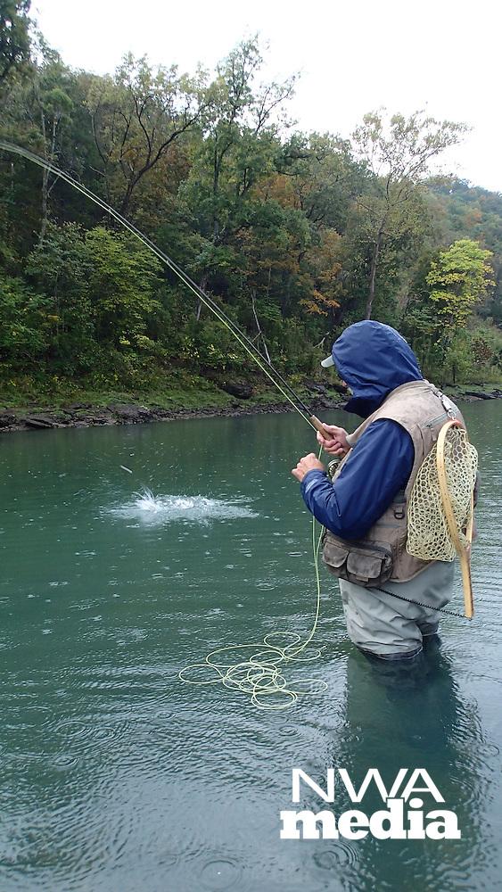 NWA Democrat-Gazette/FLIP PUTTHOFF <br /> Henderson catches a trout Oct. 8 2016 in the rain at the White River below Beaver Dam.