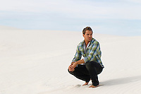 man squatting down on a white sand dune with no one else in sight in the desert