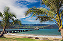 Hanalei Bay, Kauai, Hawaii with person on pier and sailboat in bay.