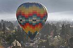 Hot air ballloons sail over Napa Valley vineyards.