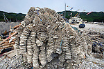 The hull of a shattered fishing boat lies atop a mountain of crushed oyster shells after being hauled out of  waters at Konabekura on the Oshika Peninsula, Miyagi Prefecture, Japan on 30 May, 2011..Photographer: Robert Gilhooly