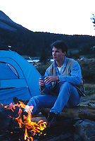 Man camping by a fire and tent in Yosemite National Park, CA