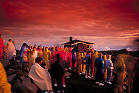 Visitors view the early morning sunrise colors in Haleakala National Park at a 9,745-ft. elevation on Haleakala. The visitor center can be seen in the background. This is one of Maui's most popular activities.
