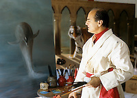 portrait of a painter working on a painting of a dolphin
