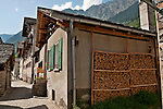 Houses and a neatly stacked wall of firewood in Soglio, Switzerland a town the Bregaglia Valley which dates back to 1219 and is said to be one of the most picturesque towns in Switzerland; Graubunden Canton