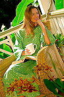 Woman Enjoys Morning Coffee On Lanai Of Her Home