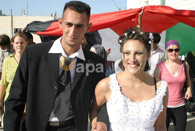 Rami Zuahreh and Rana Zuahreh celebrate their wedding ceremony during a protest against Israel's separation barrier in the West Bank village of Maasarah, near Bethlehem, Friday, July 31, 2009. The couples said they were there as a creative form of protest to show how hard it is for Palestinians to move around and live in the West Bank. Photo by Najeh Hashlamoun