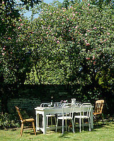 In the shade of an apple tree overgrown with pink roses a table has been laid for an al fresco lunch