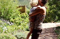 Surya Little holds her son, Eno, in the garden