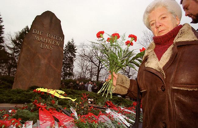Zum Gedenken an die vor 81 Jahren am 15. Januar 1919 ermordeten Rosa Luxemburg und Karl Liebknecht kamen 80.000 Menschen zur Gedenkstaette der Sozialisten nach Berlin-Friedrichsfelde. Die Veranstaltung wurde von 2.000 Polizisten, darunter etliche Scharfschuetzen, gesichert.<br /> Am Wochenende zuvor wurde das Gedenken von Polizei und Innensenat wegen einer ominoesen Anschlagsdrohung verboten.<br /> Hier: Eine Teilnehmerin der Veranstaltung legt Nelken nieder.<br /> Berlin, 15.1.2000<br /> Copyright: Christian-Ditsch.de<br /> [Inhaltsveraendernde Manipulation des Fotos nur nach ausdruecklicher Genehmigung des Fotografen. Vereinbarungen ueber Abtretung von Persoenlichkeitsrechten/Model Release der abgebildeten Person/Personen liegen nicht vor. NO MODEL RELEASE! Nur fuer Redaktionelle Zwecke. Don't publish without copyright Christian-Ditsch.de, Veroeffentlichung nur mit Fotografennennung, sowie gegen Honorar, MwSt. und Beleg. Konto: I N G - D i B a, IBAN DE58500105175400192269, BIC INGDDEFFXXX, Kontakt: post@christian-ditsch.de<br /> Bei der Bearbeitung der Dateiinformationen darf die Urheberkennzeichnung in den EXIF- und  IPTC-Daten nicht entfernt werden, diese sind in digitalen Medien nach &sect;95c UrhG rechtlich gesch&uuml;tzt. Der Urhebervermerk wird gemaess &sect;13 UrhG verlangt.]