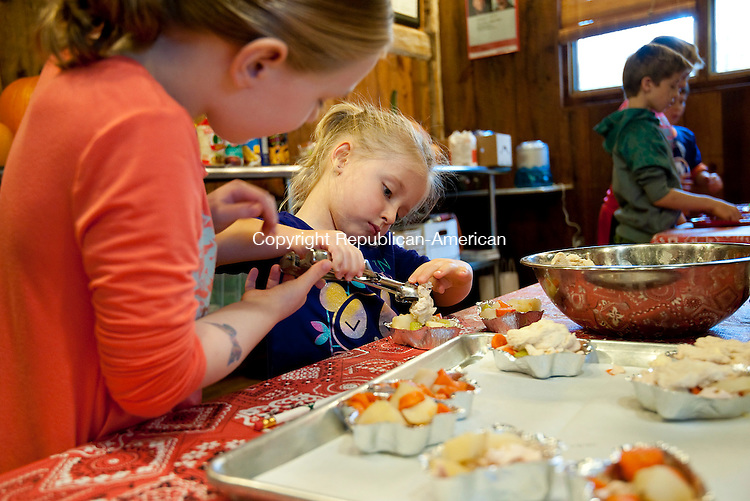 WASHINGTON, CT--- -102515JS01---Maryn Heinrich, 5, of Woodbury, right, gets some help from her cousin Jamie Hendrix, 7, of Woodbury, as they put the finishing touches on their chicken pot pies during a Halloween Magic children's cooking class Sunday at The Silo at Hunt Hill Farm in Washington. Jim Shannon Republican-American