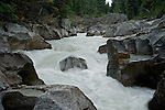 The greyish-white water due to the minute particles of rock and dirt flowing over the dark rocks in Nigel Creek