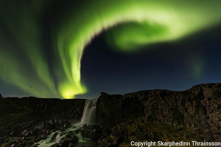Aurora borealis over Öxarárfoss in Þingvellir National Park, southwest Iceland