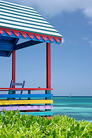 The covered terrace of this multi-coloured beach hut looks out over the azure blue waters of the ocean