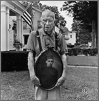 Mr. E Paul Martin.age 102 holding a photograph of himself at age 19 a soldier in WW1. South Main St. New Milford, CT