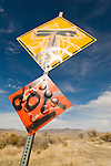 Yellow and red diamond traffic warning signs: T intersection and end of roadway with painted graffiti, Nevada