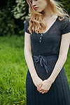 Young woman with long blonde hair wearing a black dress in field with hands clasped