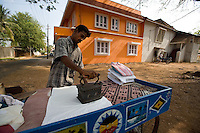 20080203_Fort Kochin, India_ A man uses an iron heated by burning coconut shells to press cloths on a street corner in Fort Kochin, which is located in the Southern Indian state of Kerala.  Photographer: Daniel J. Groshong/Tayo Photo Group