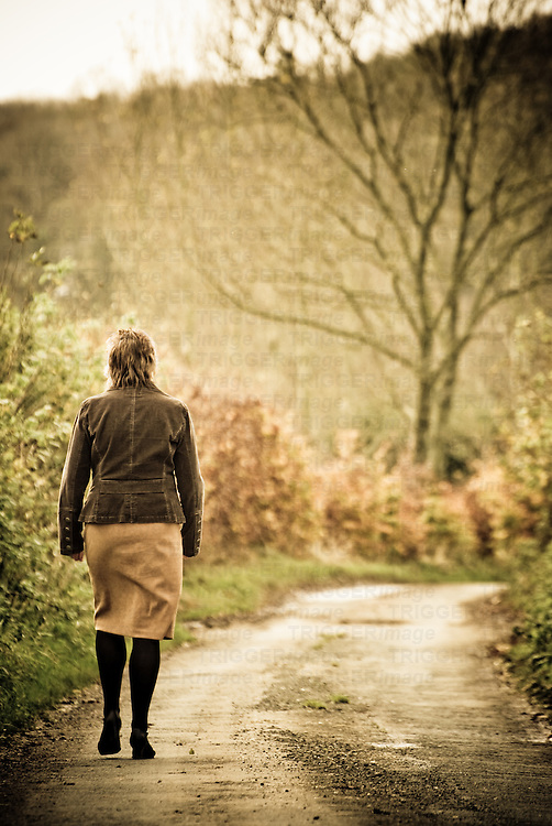 A middle aged woman walking alone along a lane in Autumn away from the camera