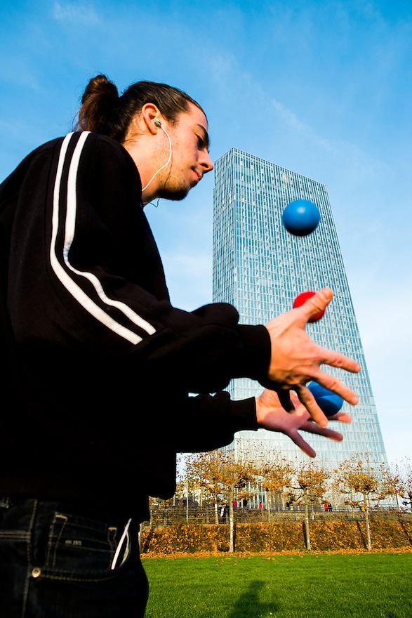 Duitsland, Frankfurt am Main, 23 nov 2014<br /> Het gebouw van de Europese Centrale Bank ECB<br /> Headquarters of the European Central Bank ECB<br /> Een jongleur oefent zijn techniek, bij de ECB proberen ze op een andere manier de balletjes in de lucht te houden<br /> Foto: (c) Michiel Wijnbergh