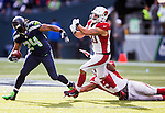 Seattle Seahawks running back Marshawn Lynch stiff arms Arizona Cardinals linebacker Larry Foote (50) while running for a 13-yard gain at CenturyLink Field in Seattle, Washington on November 23, 2014. The Seahawks beat the Cardinals 19-3.  ©2014. Jim Bryant Photo. All Rights Reserved.