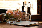 Table at a cafe in Como, Italy.  A menu, salt and pepper, olive oil, and a vase of pink roses sits on a table in a cafe in Como, Italy.