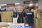 Nov. 23, 2012 - Bellmore, New York, U.S. - On Black Friday, the big shopping day after Thanksgiving, these customers are shopping locally at P.C. Richard & Son, an appliance and electronics chain that has sales and is decorated for the winter holidays. Staff helped customers take large items purchased, such as this big television, to their vehicles. PC Richard & Son has been a local presence in Bellmore, Long Island, since 1953.