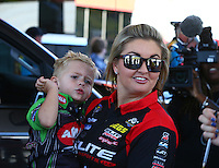 Jun 19, 2016; Bristol, TN, USA; NHRA pro stock driver Erica Enders-Stevens holds Cameron McMillen , son of Terry McMillen (not pictured) during the Thunder Valley Nationals at Bristol Dragway. Mandatory Credit: Mark J. Rebilas-USA TODAY Sports