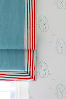 Detail of a striped blind hanging across a polar bear wallpaper in a child's bedroom