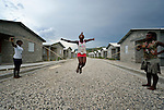 """Children jump rope in a model resettlement village constructed by the Lutheran World Federation in Gressier, Haiti. The settlement houses 150 families who were left homeless by the 2010 earthquake, and represents an intentional effort to """"build back better,"""" creating a sustainable and democratic community."""
