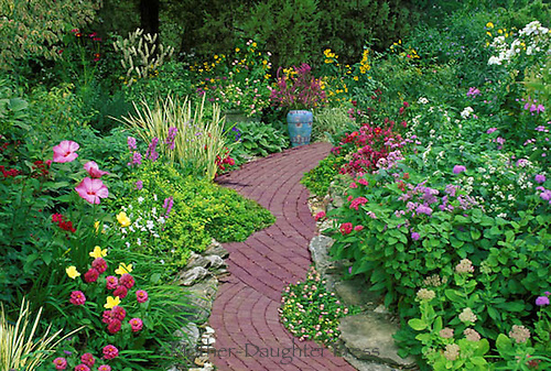 Brick path in scalloped pattern with blooming flowers in pastel colors and Mexican pottery vase as sculpture