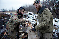 """UKRAINE, 02.2016, Oblast Donetsk. Ukrainian-Russian conflict concerning Eastern Ukraine / Foreign volunteers (""""Task Force Pluto"""") fighting with the far-right militia Pravyi Sektor against the Russian-backed separatists: Ben (Austria) and Craig (USA) fill a bag with wet fire wood for their trench positions close to the Donetsk frontline. © Timo Vogt/EST&OST"""