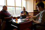 Two men and a woman play cards in a pub in Pembroke, Wales, the United Kingdom.