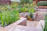 Sunken patio outdoor room landscaping, stone steps, garden gazebo and bench with cushions, water feature garden with waterlilies, lush flowers in green and gold and yellow color theme, wall fence, levels, home garden