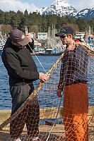 Fishermen repair holes in purse seine net for Herring, Sitka, Alaska
