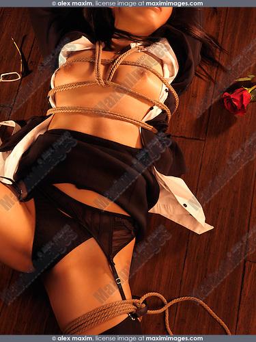 Beautiful half-naked asian woman lying on the floor tied up with Japanese rope bondage Shibari