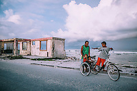 A man with his children riding a tricycle near an abandoned house on the shore of Ebeye island. Due to the erosion of the coastline, several houses have been destroyed.