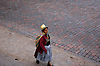 CUZCO PERU WOMAN WALKS ALONG THE BRICK-PAVED ROADS IN TOWN