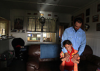 """Hawaiian cowboy, Wayne Tachera and his daughter, Nahe, 9, share a tender moment at their home on Kahua Ranch in North Kohala, Hawaii. The house is part of """"cowboy housing"""" which is subsidized by the ranch as part of a cowboy's benefit package. """"We get free housing, free electricity, free water.  It makes up for cowboy pay because cowboy pay is not much at all"""","""" says Tachera.  Nahe and her sister, Kamehana, are very close to their father who taught them to ride horses as toddlers and took them to work with him when childcare wasn't available."""