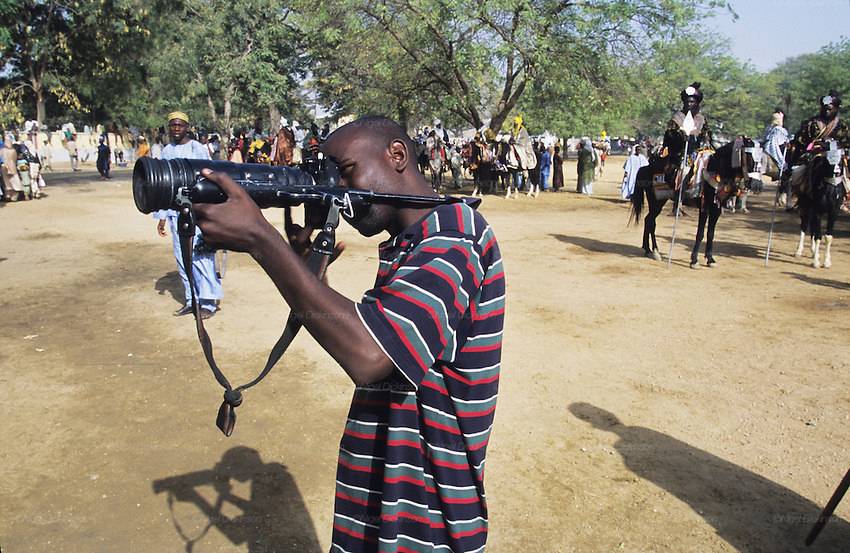 A local photographer with a Zenith sniper camera photographs during the Durbar Fantasia..The Durbar Fantasia, is the moment where The Husa residents of Kano wear traditional dress, their local leaders and chiefs mount horses, and together with their militias display allegiance and homage to their leader, the Emir of Kano. This takes place after Ramadan. The Emir is Kano's State official political and economic feudal leader, everyone seeks to be in his pleasure, otherwise they reap the consequences..Kano is the largest Muslim Husa city, under the feudal, political and economic rule of the Emir. Kano and the other eleven northern states are under Islamic Sharia Law which is enforced by official state apparatus including military and police, Islamic schools and education, plus various volunteer Militia groups supported financially and politically by the Emir and other business and political bodies. 70% of the population live below the poverty line. Kano, Kano State, Northern Nigeria, Africa