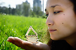 Young woman looking at a house made from matches on her hand in summer  nature environment. Home renovation future house real estate housing property insurance concept
