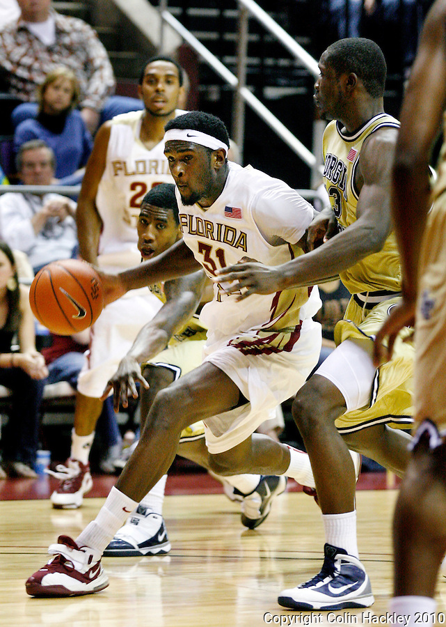 TALLAHASSEE, FL 1/24/10-FSU-GA. TECH MBB10 CH30-Florida State's Chris Singleton drives between Georgia Tech's Iman Shumpert, left, and D'Andre Bell during second half action Sunday at the Donald L. Tucker Center in Tallahassee. The Seminoles beat the Yellow Jackets 68-66...COLIN HACKLEY PHOTO