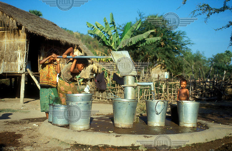Chidlren pumping water from a village well.